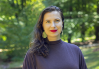 Marina Dunaravich standing with foliage behind her.